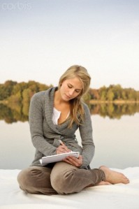 Young woman writing,sketching, by lake
